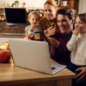 Family of 4 with two young children having a video chat on a computer.