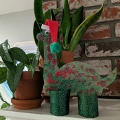 Christmas Dino Decoration - finished dino decoration on the mantel next to two potted plants