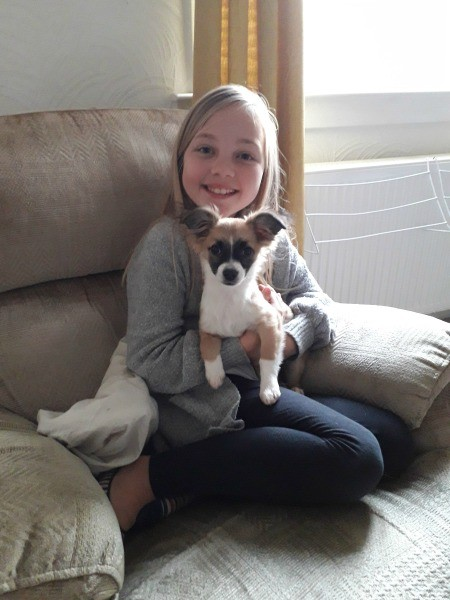 A girl holding a small dog on the couch.