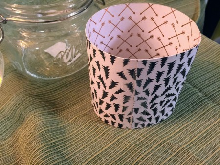 Rolling a piece of cardstock to fit inside the jar.