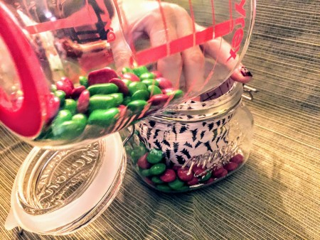 Adding candy to the jar.