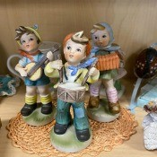 A figurine of three children playing music.