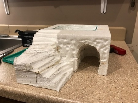 The styrofoam carved with a cave for a reptile.