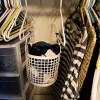 A basket hanging from two hangers in the closet.