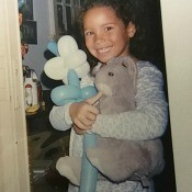 A girl holding a grey stuffed rabbit.