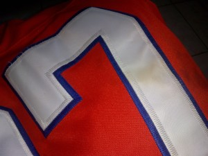 A yellow stain on the white number on a jersey.