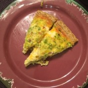 A plate with two slices of quiche.