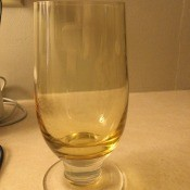 A footed glass with a yellow tint.