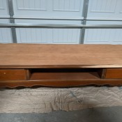 A low wooden table with drawers.