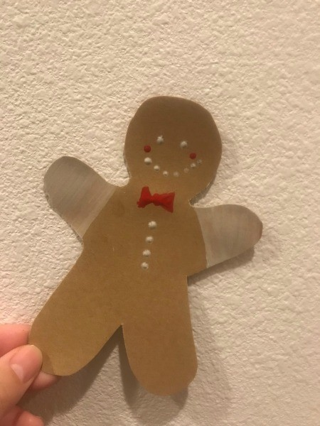 A gingerbread man with a face, buttons and bow tie.