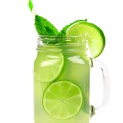 A glass jar filled with limeade and mint.
