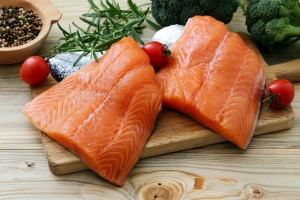 Two salmon fillets on a cutting board.