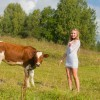 A girl near a cow in a grassy field.