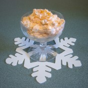 A footed glass bowl of orange pineapple fluff.