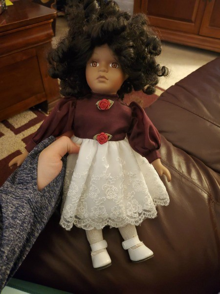 Identifying a Porcelain Doll? - ethnic doll wearing a dress with brown bodice and white lace skirt