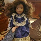 Identifying a Porcelain Doll? - dark skinned doll wearing a blue dress with white lace trim