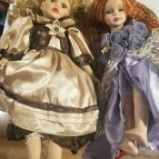 Two porcelain dolls in fancy dresses.