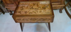 An ornately carved wooden end table.