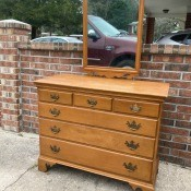 A wooden dresser with a mirror.