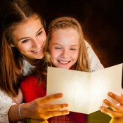 A mother and daughter reading a poem at Christmas time.