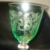 A green glass goblet with a clear stem.