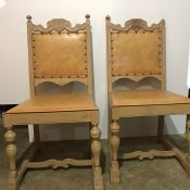 A set of wooden chairs with leather seats and backs.
