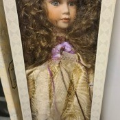 A porcelain doll in original packaging.