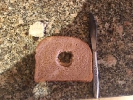 Cutting a hole in bread for the egg.