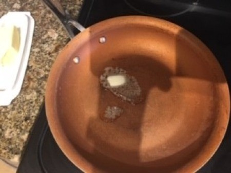 Butter melted into a frying pan.