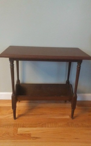 A wooden side table with a lower shelf.