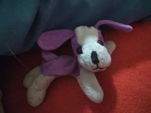 A small purple and white stuffed dog.