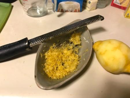 Finely zesting lemon peel.
