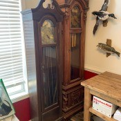Two wooden grandfather clocks.