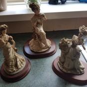 Three figurines of fancy ladies.