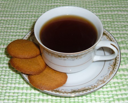 Ginger snaps next to a cup of coffee.