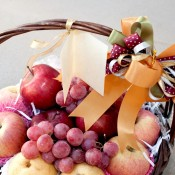 A fruit basket with apples and grapes.