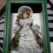 A doll in a shadowbox frame.
