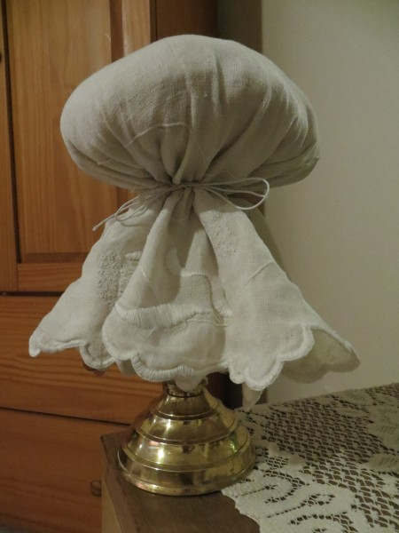 A cloth draped over the top of the foam covered candlestick.