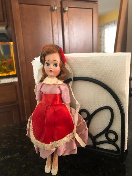 A plastic doll with a red dress.