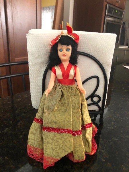 A dark haired doll with a fancy dress.