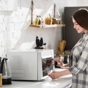 A woman using a microwave.