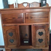 A wooden piece of furniture with heart decorations.