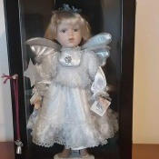 An angel doll in a glass case.