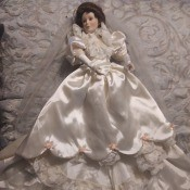 A porcelain doll in a white dress.