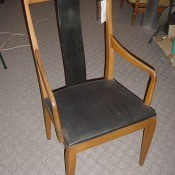 A wooden dining chair with arms.