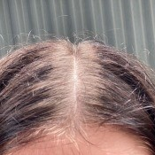 A woman hair with lighter roots.