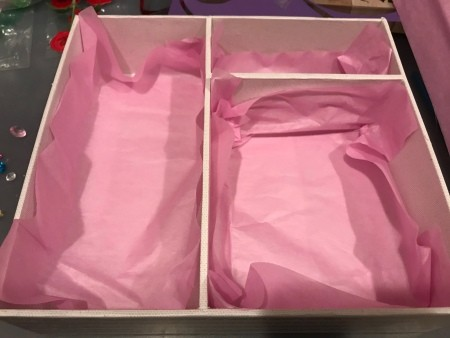 Lining the inside of a box with pink tissue paper.