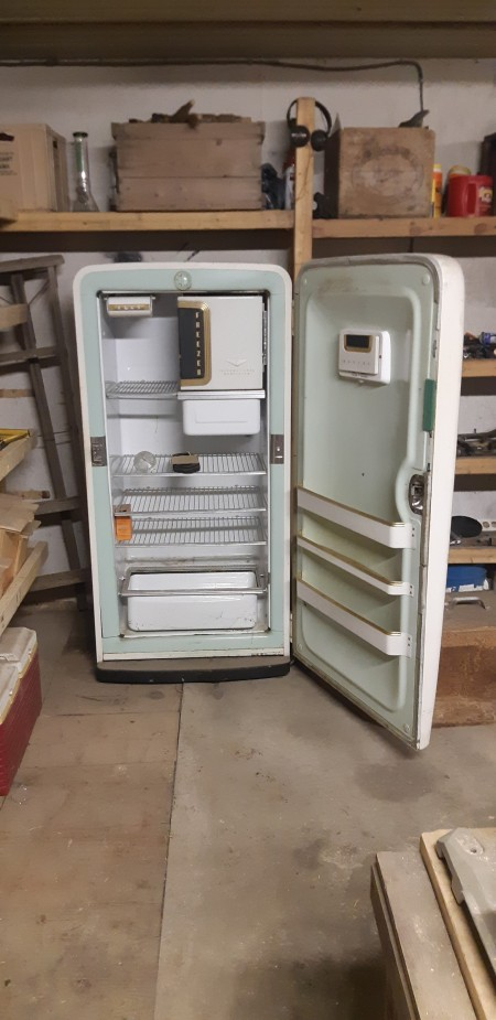 An old white refrigerator with the door open.