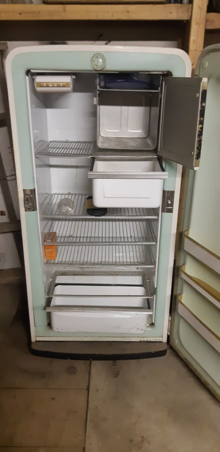 An old white refrigerator with both doors open.