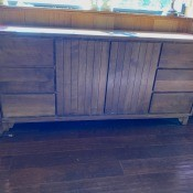 A wooden credenza with doors and drawers.